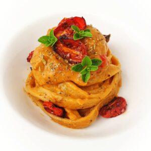 Tagliatelle fresce integrali con crema di melanzane, capperi, robiola e cuore di pomodoro, datterini confit e origano fresco.